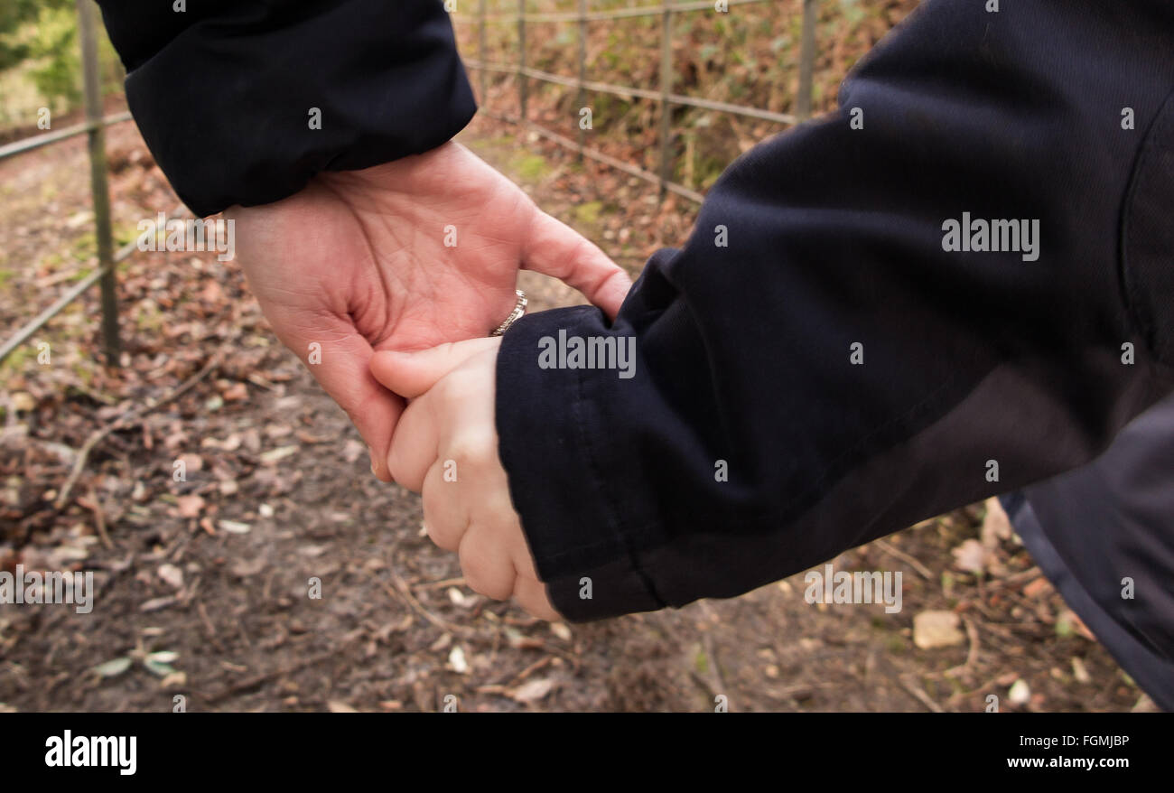 A mother guiding her son holding hands - Stock Image