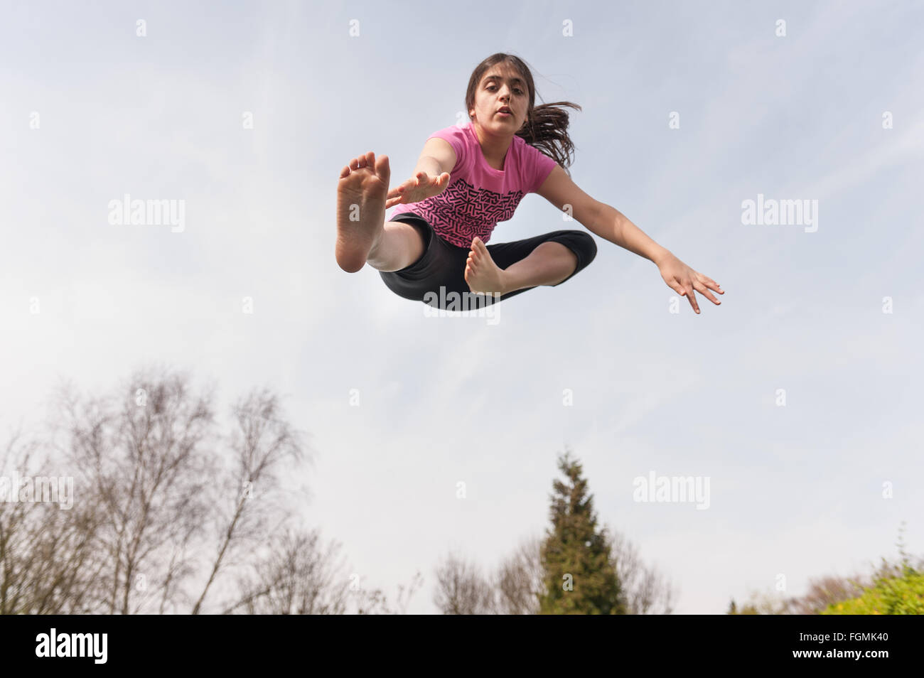 Teenager jumping high in the air bouncing off a trampoline doing acrobatics - Stock Image
