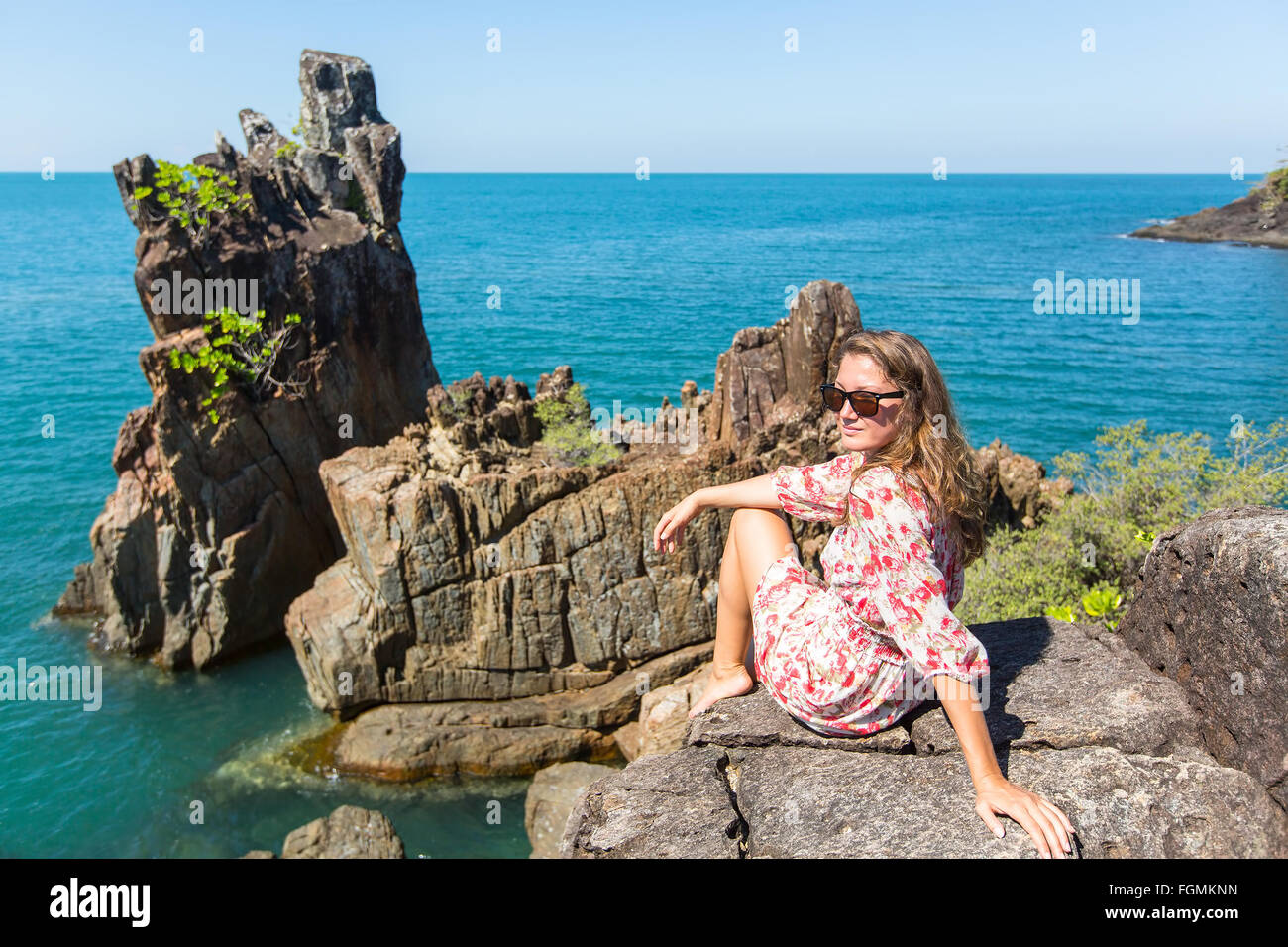 Young woman sitting on coastal rocks of Koh Chang island in Thailand. Stock Photo