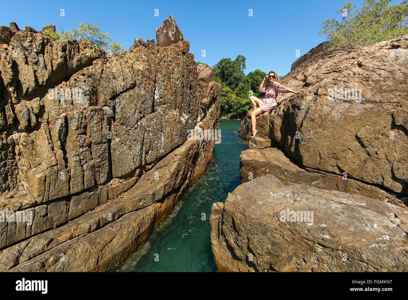 Beautiful woman sitting on coastal rocks of Koh Chang island in Thailand. - Stock Image