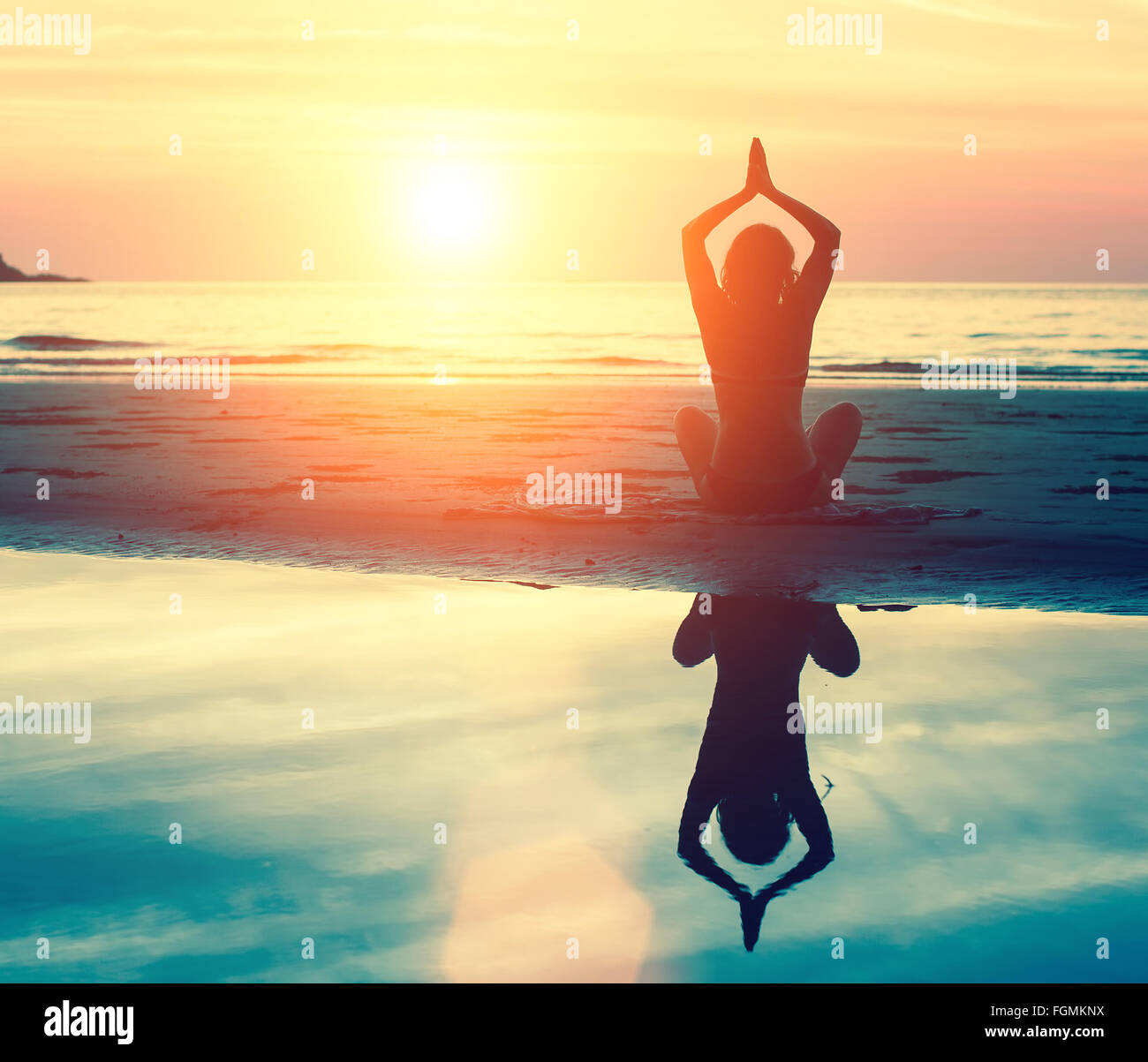 Meditation, serenity and yoga practicing at sunset. - Stock Image