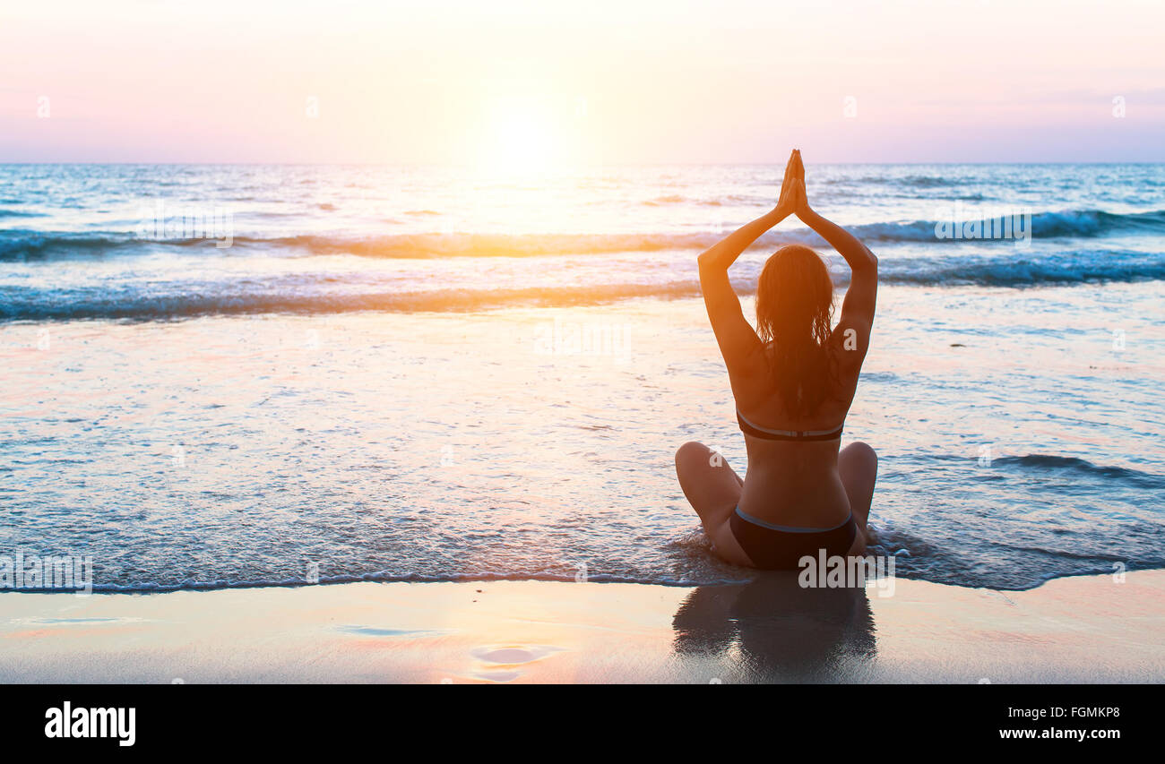 Silhouette woman practicing yoga on the beach at sunset. - Stock Image
