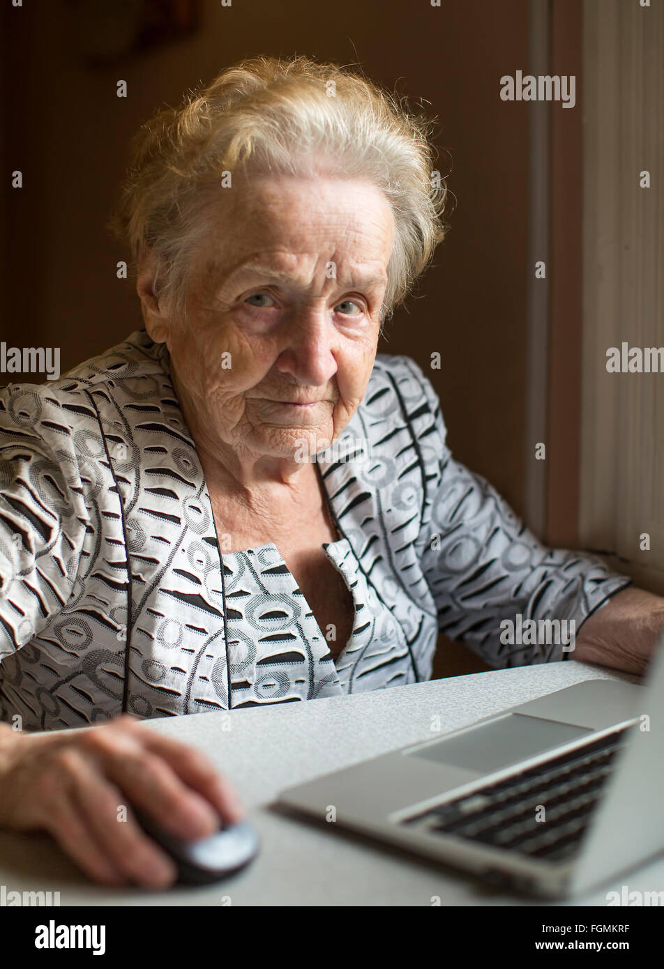 An elderly woman sitting with laptop. - Stock Image