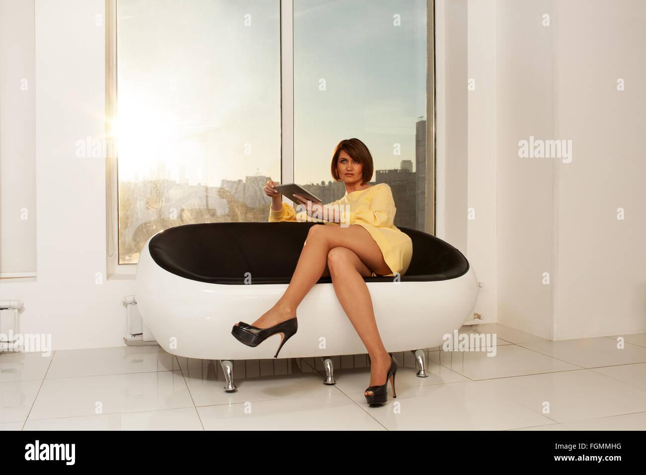 Elegant businesswoman sitting on sofa with crossed legs - Stock Image