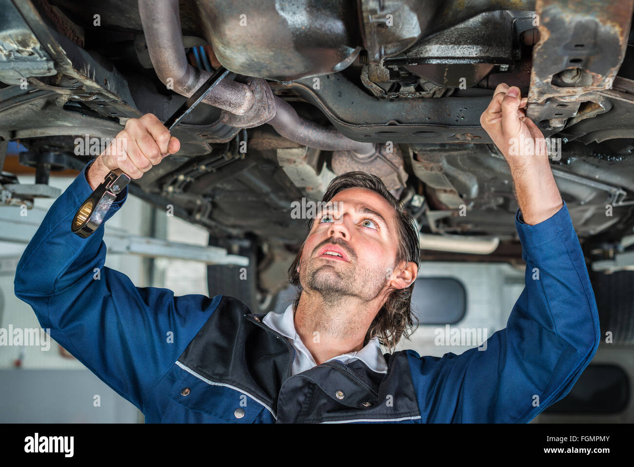 Mechanic repairing a lifted car wit - Stock Image