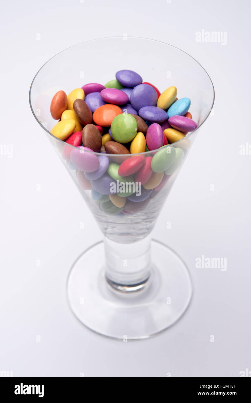 Wine glass full of multicoloured chocolate Smarties - Stock Image