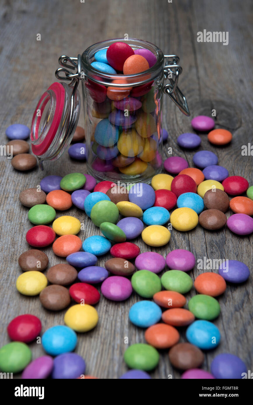 A glass jar full of chocolate coated Smarties - Stock Image