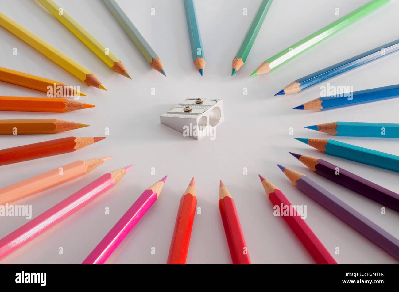 Colored pencils surrounding menacingly a pencil sharpener. - Stock Image