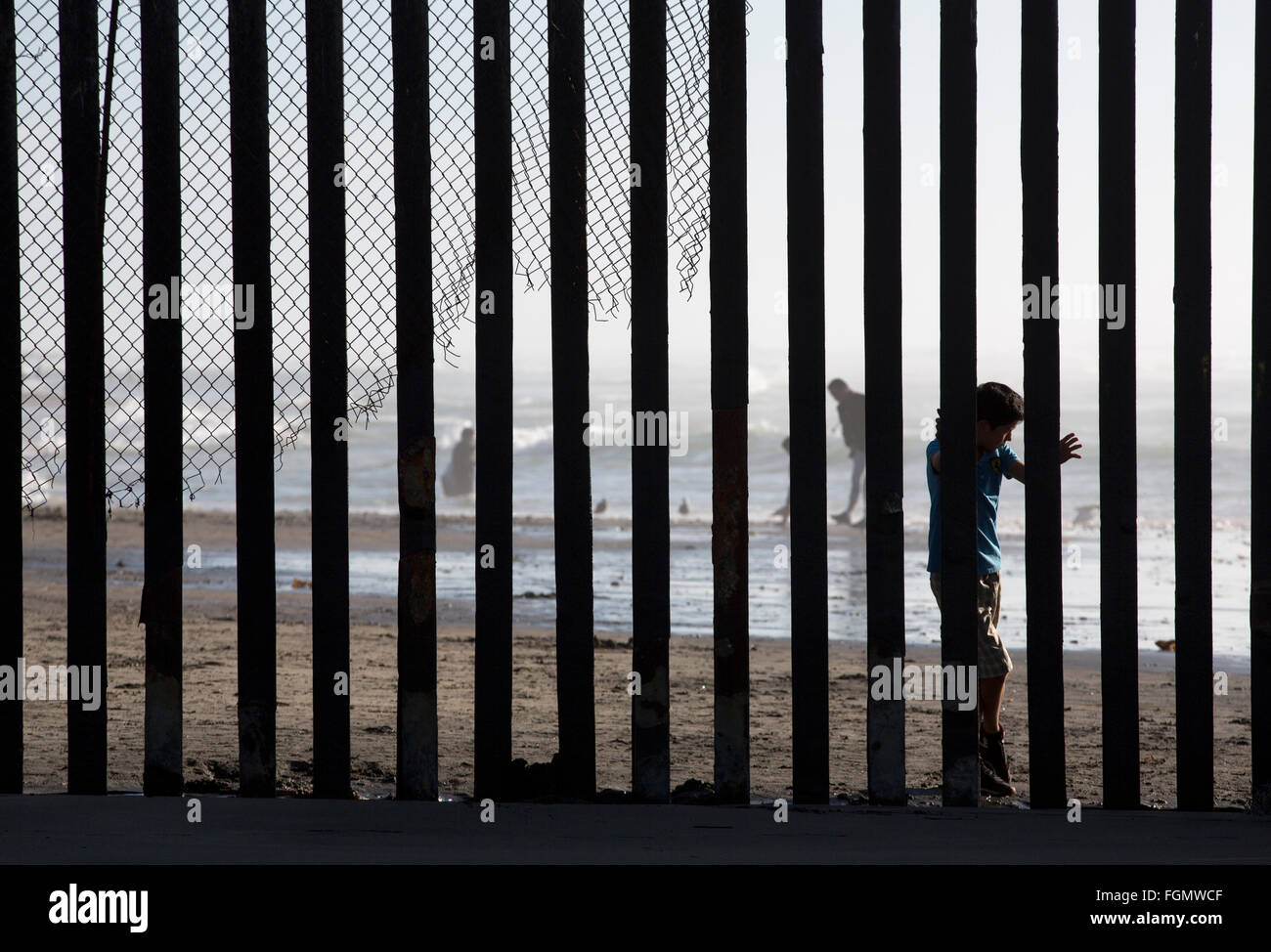 A boy peers through the border fence as seen from the American side US / Tijuana, Mexico border near San Ysidro, - Stock Image
