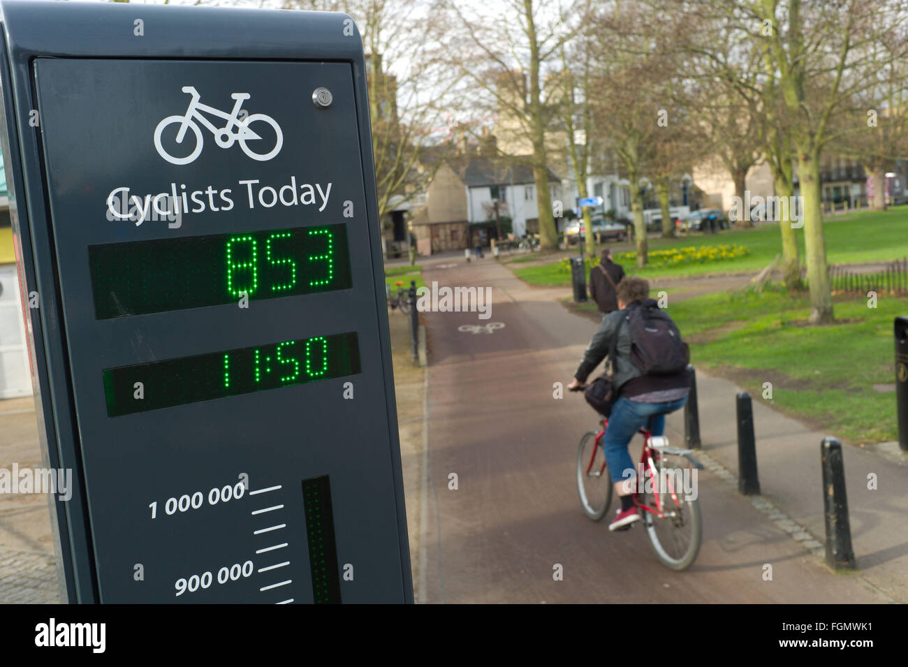 Cyclist passing a sign in Cambridge UK that shows the number of cyclists that have used the cycle track that day - Stock Image