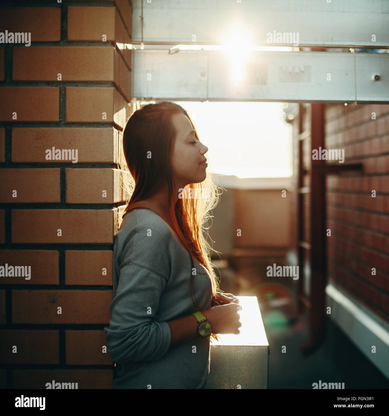 Young Woman Standing on a Street with Closed Eyes in Sunset Light. Selective Focus, Lens Flare. - Stock Image