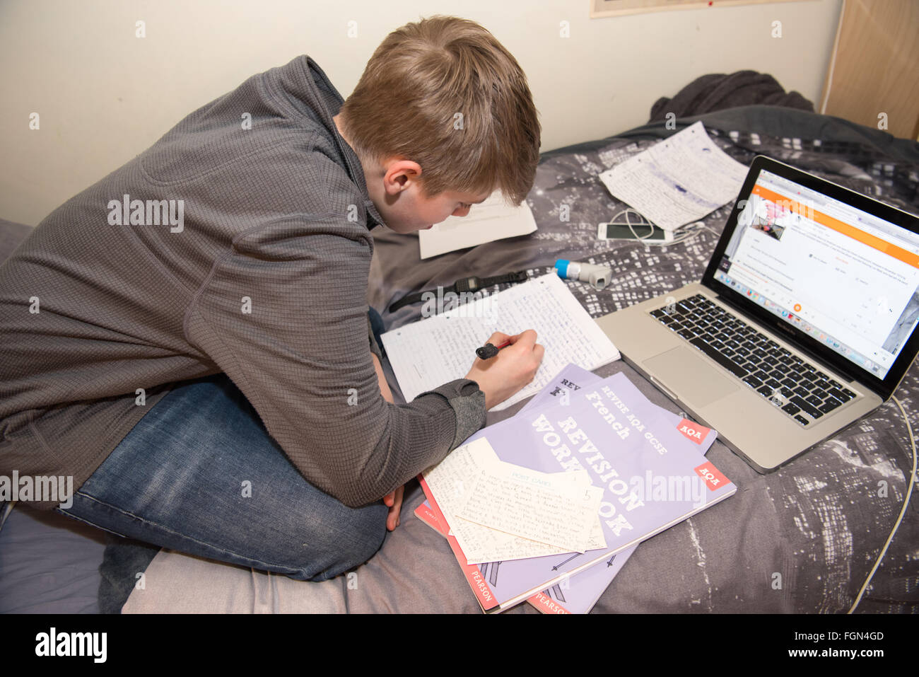 White teenage boy sitting on his bed with a laptop and lots of school books as he revises for GCSE exams and makes - Stock Image