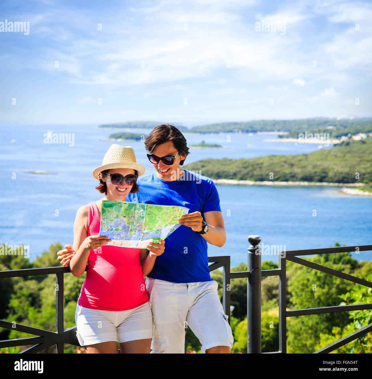 Couple Looking at Map by the Sea - Stock Image