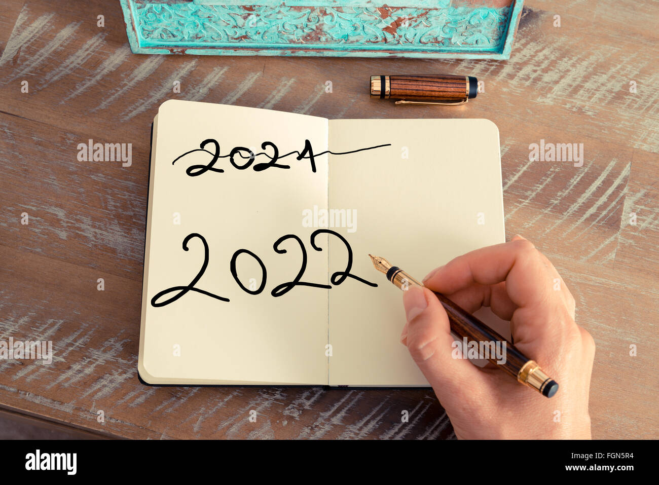 Retro effect and toned image of a woman hand writing a note with a fountain pen on a notebook. Motivational concept - Stock Image