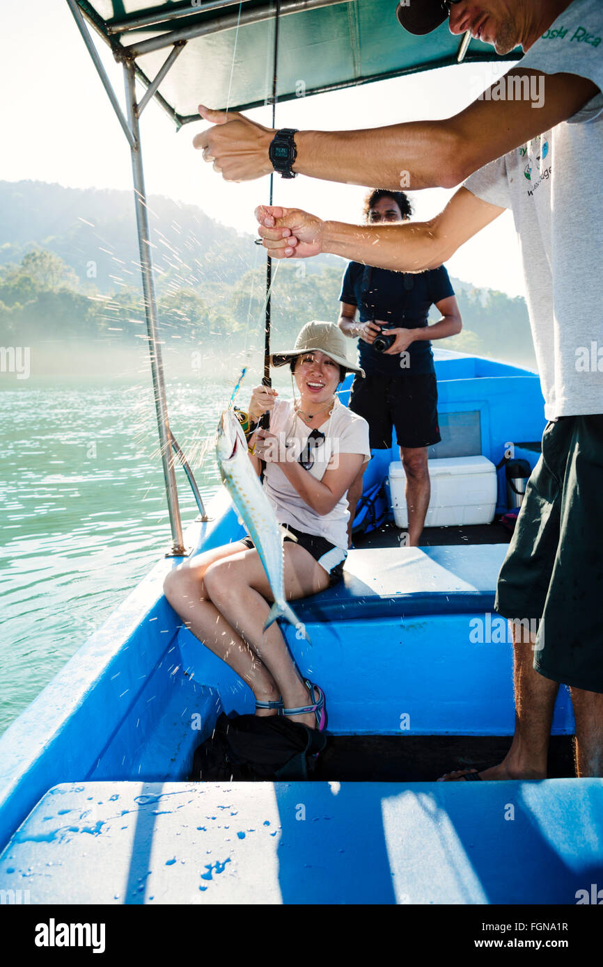 An Asian female tourist sports fishing with a dripping fish fresh on the line - Stock Image