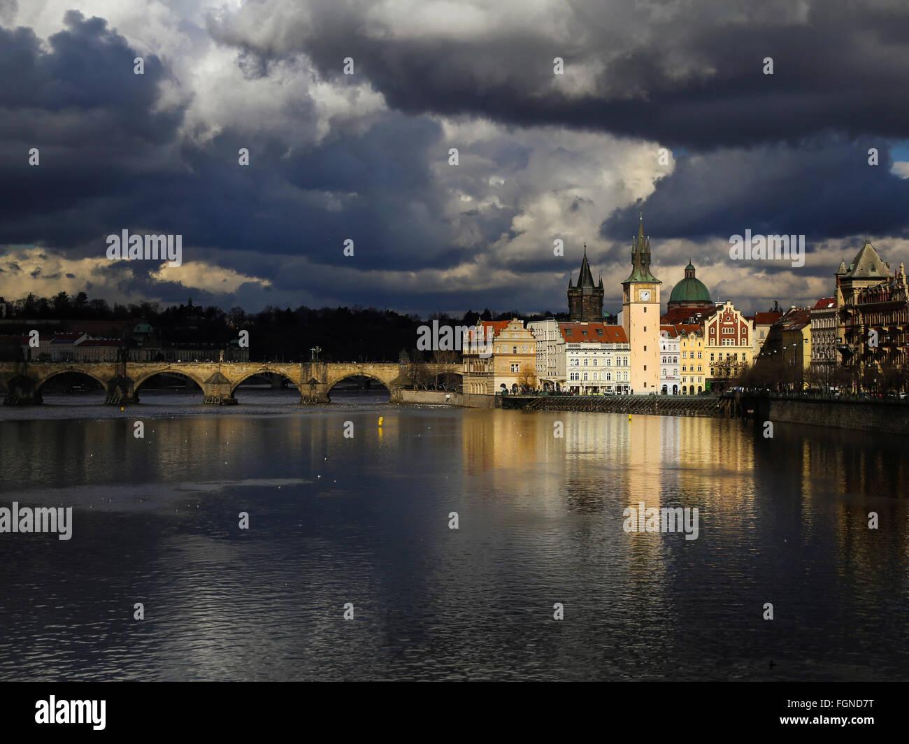 Charles bridge and Vltava riverside with dramatic sky (Prague, Czech Republic) - Stock Image