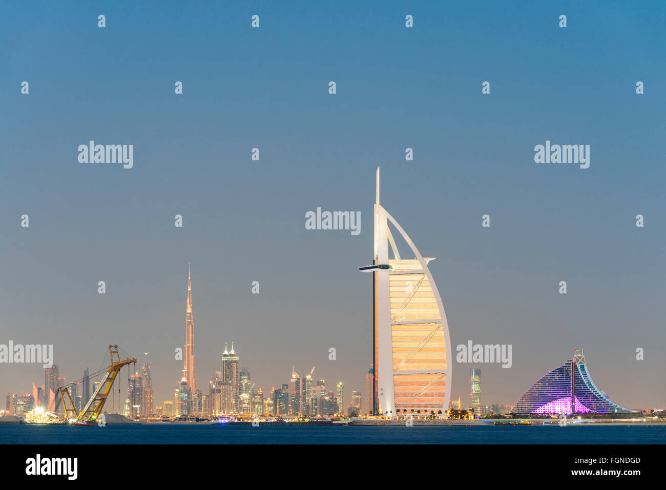 Skyline at night of Dubai waterfront with Burj al Arab Hotel in United Arab Emirates - Stock Image