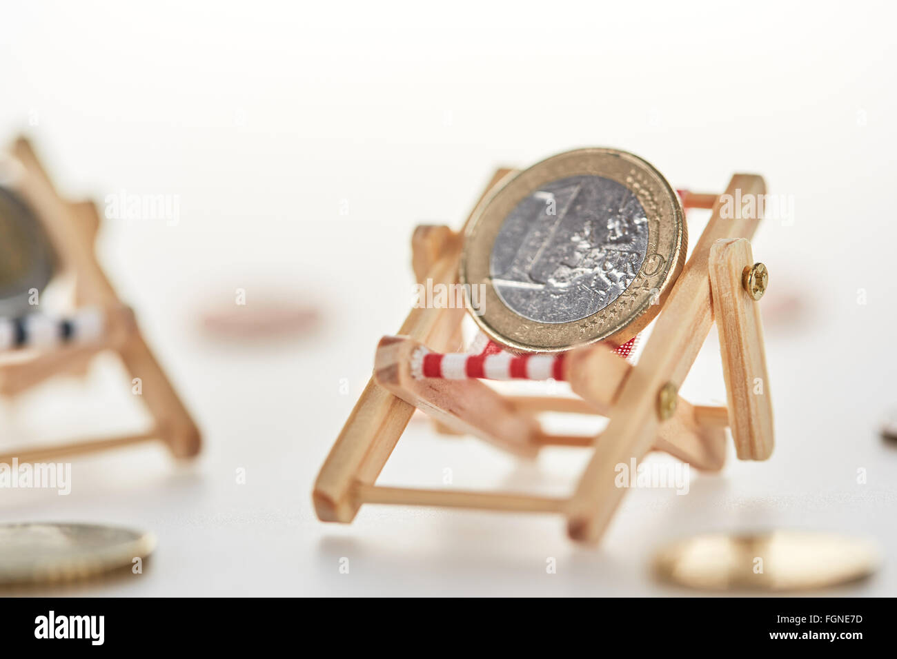Pension concept shot with euro coin money relaxing on miniature lounger - Stock Image