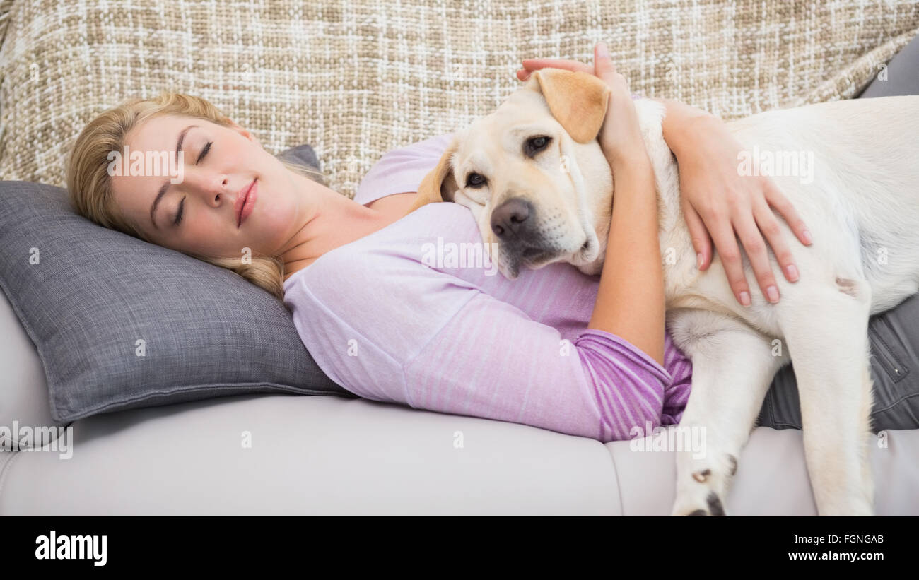 Beautiful blonde on couch with pet dog Stock Photo