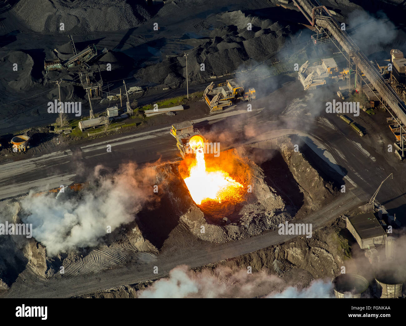 Glowing hot slag from iron production is tipped from a ladle car into a pit, slag car at the Krupp Mannesmann steelworks, - Stock Image
