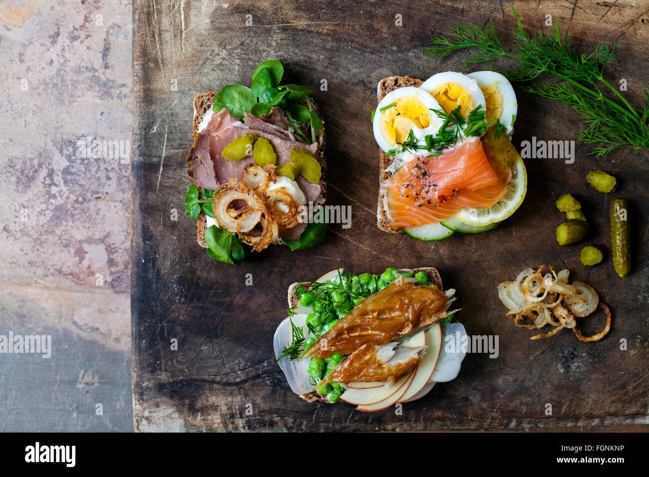 Scandinavian open sandwiches with smoked mackerel, salmon and egg and roast beef and crispy onion - Stock Image