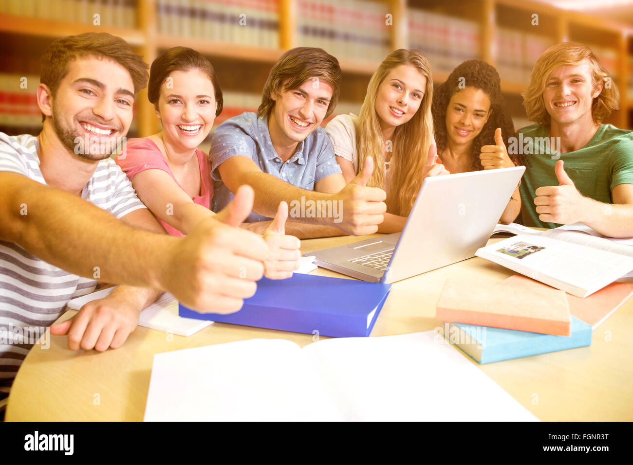 Composite image of college students gesturing thumbs up in library - Stock Image