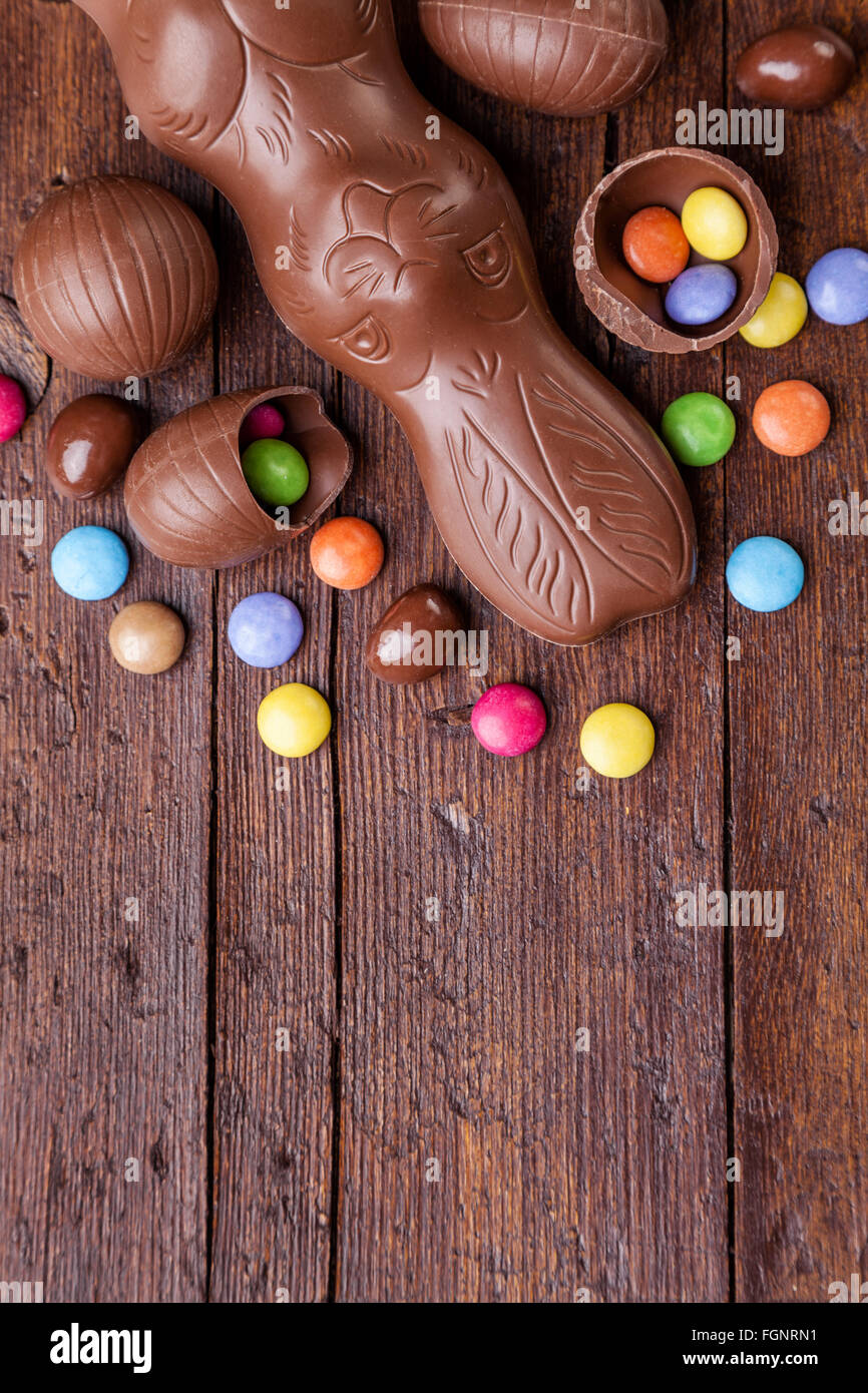 Delicious chocolate easter eggs and sweets on wooden background - Stock Image