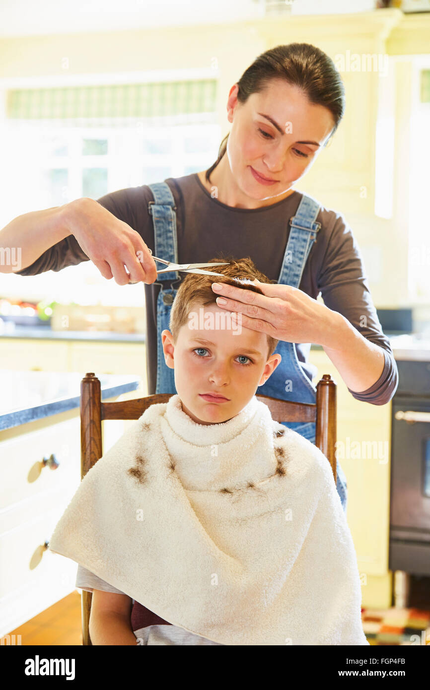 Portrait unhappy boy getting haircut from mother in kitchen - Stock Image