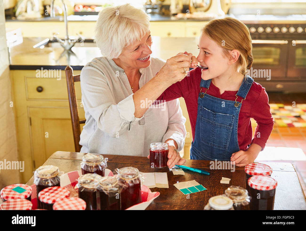 Grandmother and granddaughter canning jam in kitchen - Stock Image