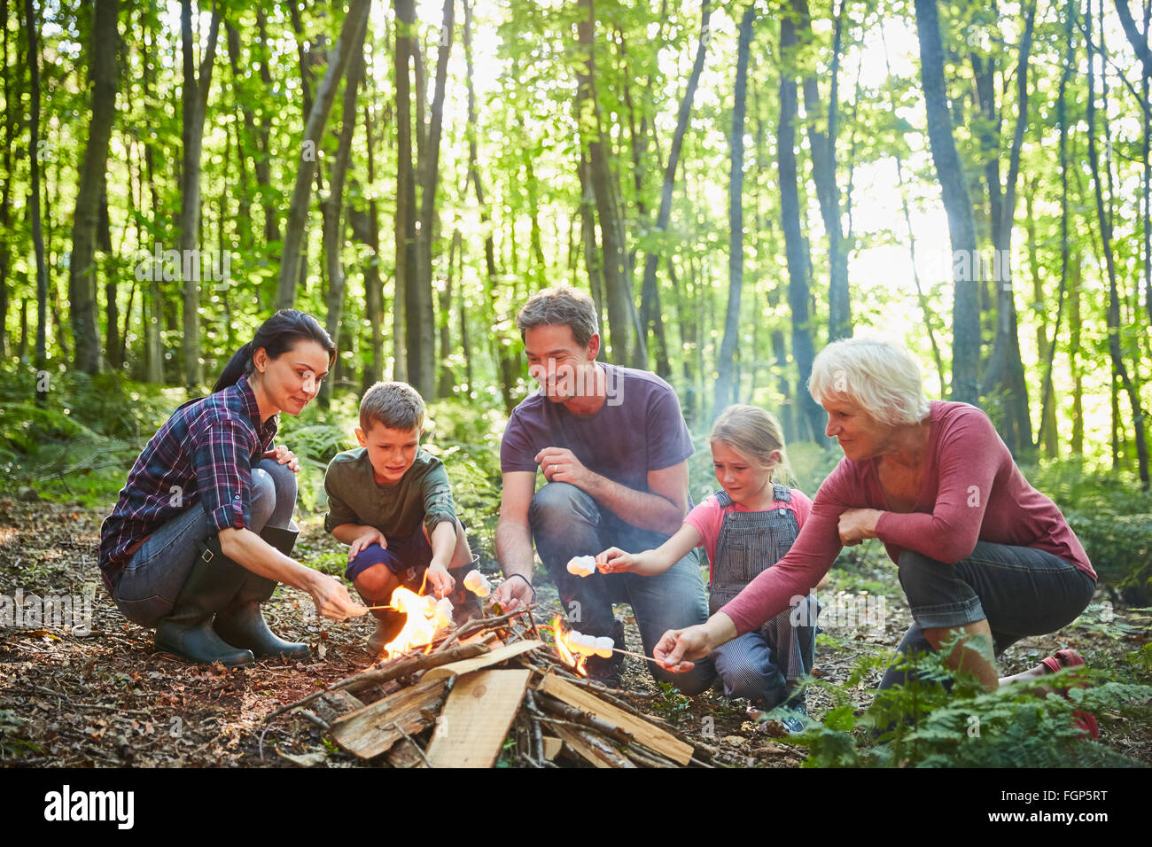 Multi-generation family roasting marshmallows at campfire in forest - Stock Image