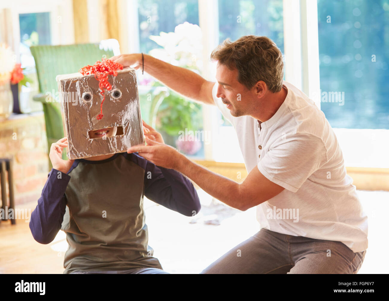 Father placing robot mask on son - Stock Image