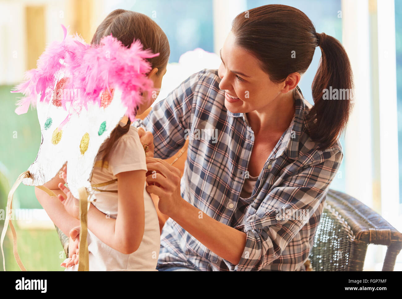 Mother fitting wings on daughter - Stock Image