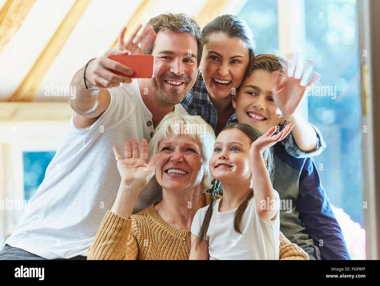 Multi-generation family waving and taking selfie - Stock Image