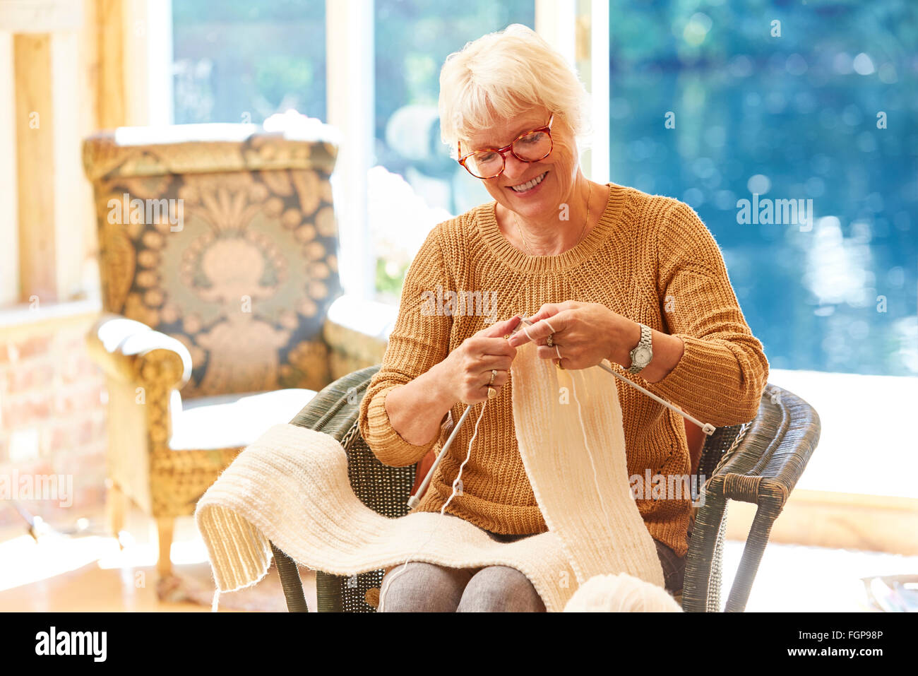 Senior woman knitting in living room - Stock Image