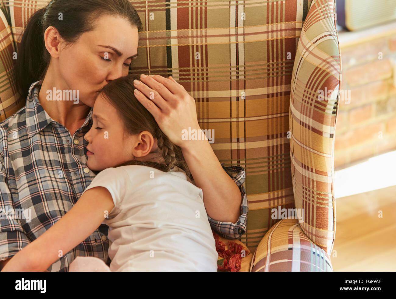 Tender mother cuddling sleeping daughter in armchair - Stock Image