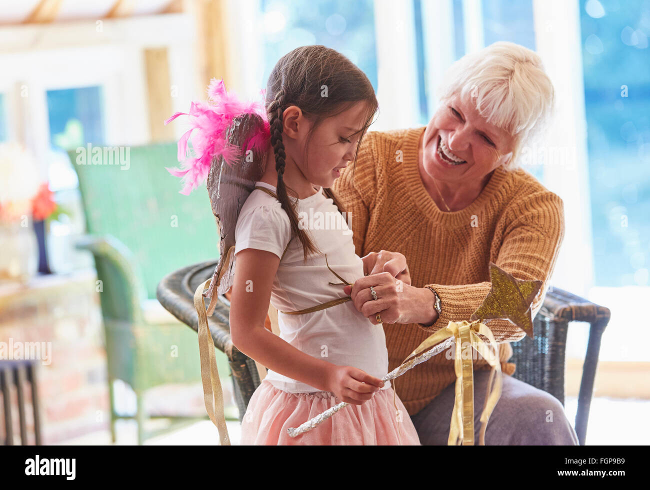 Grandmother fitting granddaughter with wings - Stock Image