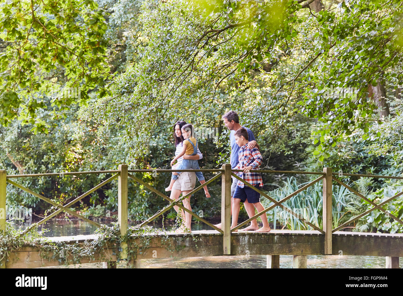 Family crossing footbridge in park with trees - Stock Image