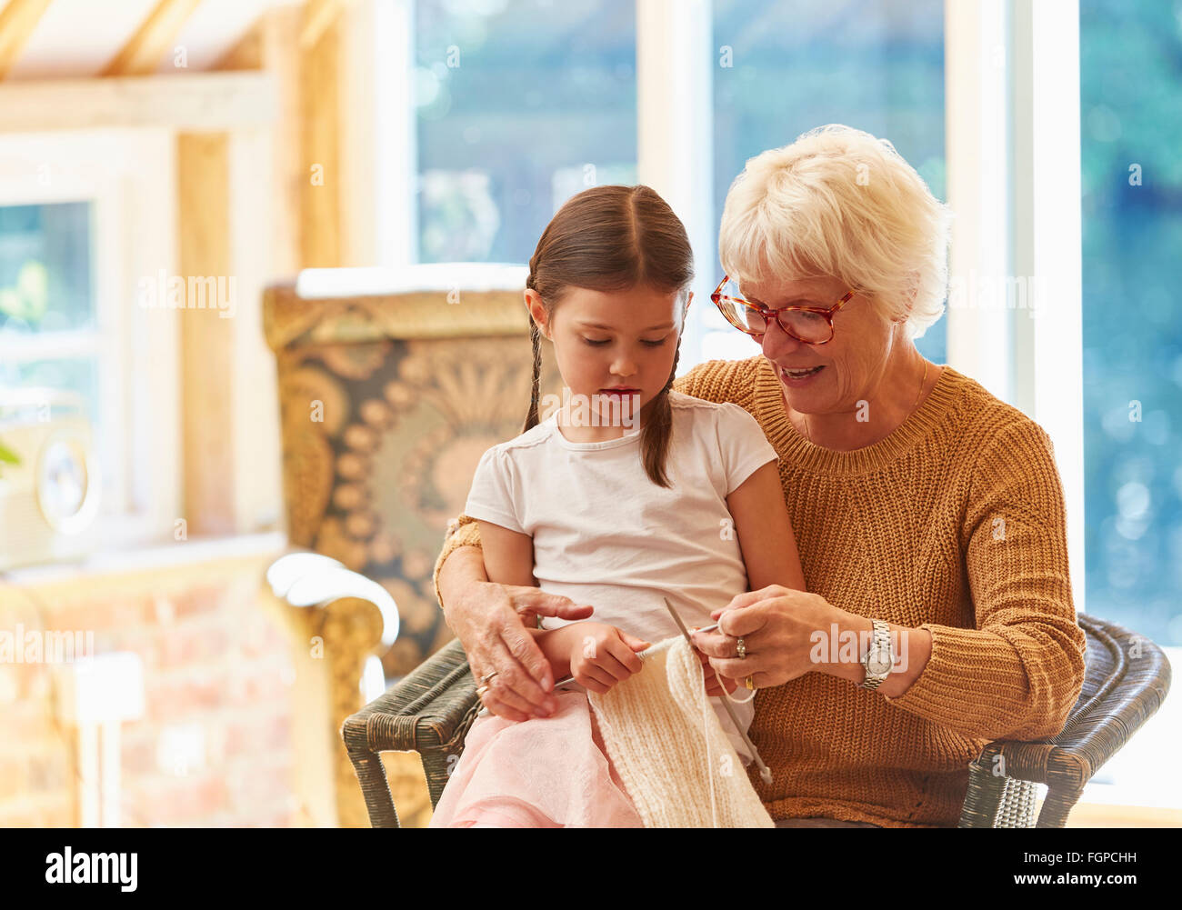 Grandmother teaching granddaughter knitting - Stock Image