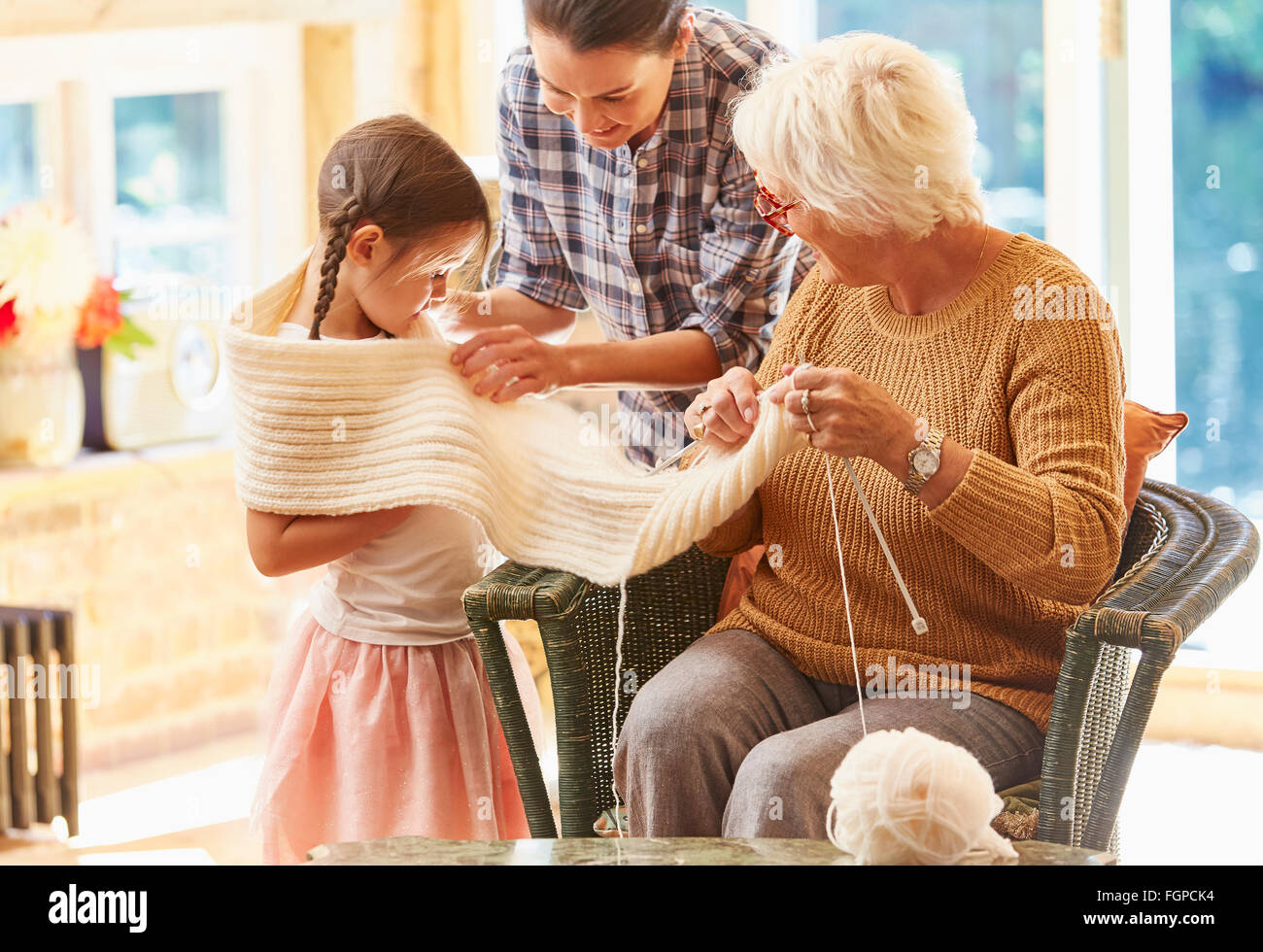 Grandmother knitting scarf around granddaughter - Stock Image