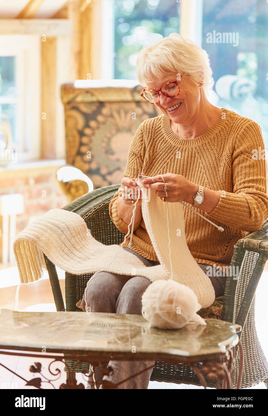 Smiling senior woman knitting scarf - Stock Image