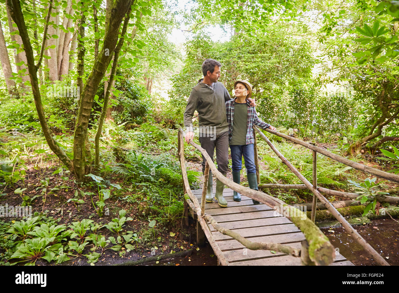 Father and son crossing footbridge in forest - Stock Image