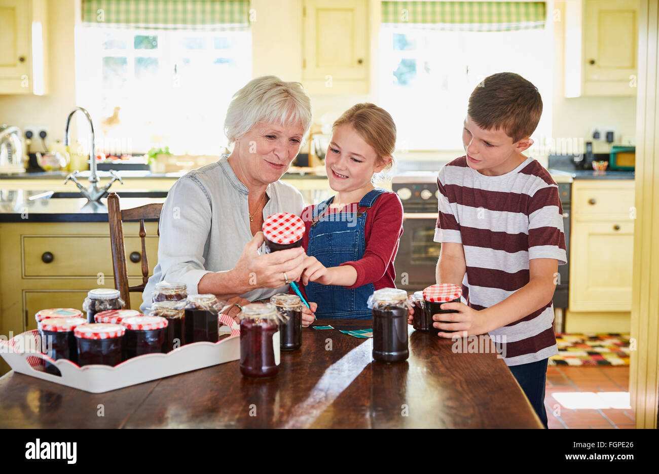 Grandmother canning jam with grandchildren in kitchen - Stock Image
