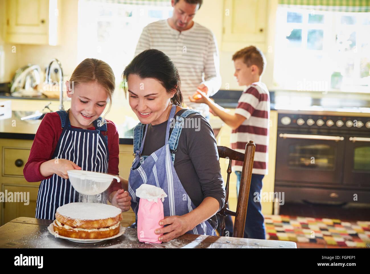 Family baking cake in kitchen - Stock Image