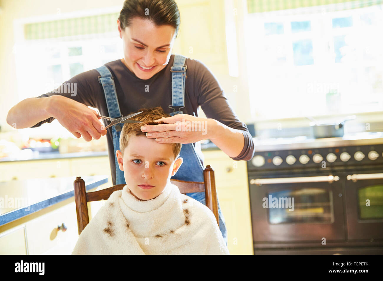 Unhappy boy getting haircut from mother in kitchen - Stock Image