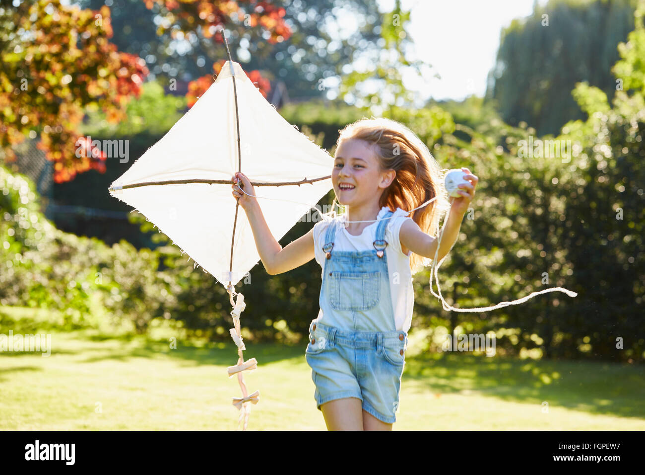 Enthusiastic girl running with kite in sunny garden - Stock Image