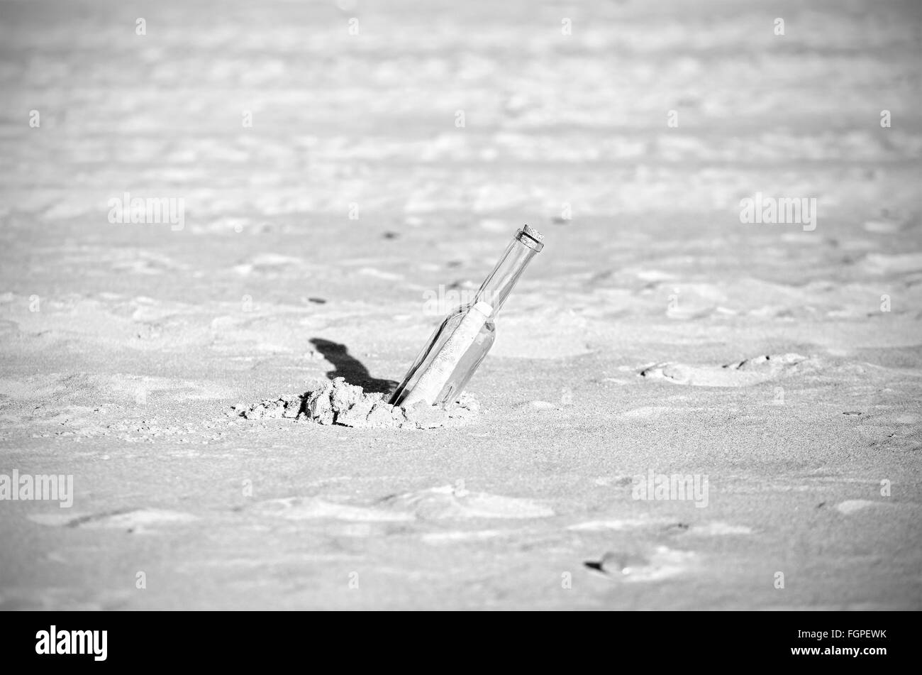 Black and white message in a bottle on sand, shallow depth of field. - Stock Image