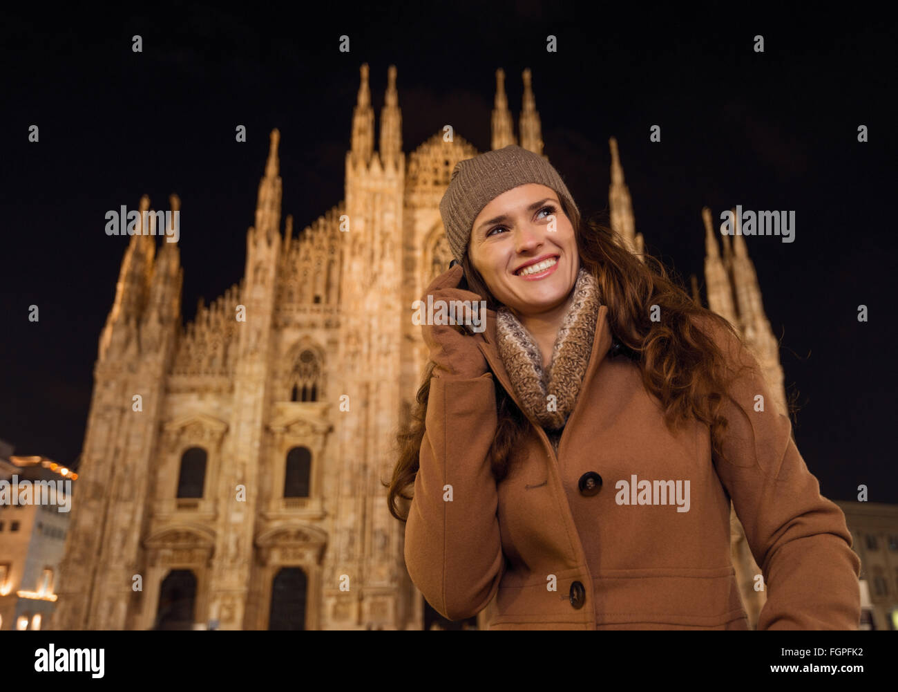 It is time to dress up and take a night tour in ultra-luxurious fashion expert - Milan, Italy. Happy young woman - Stock Image