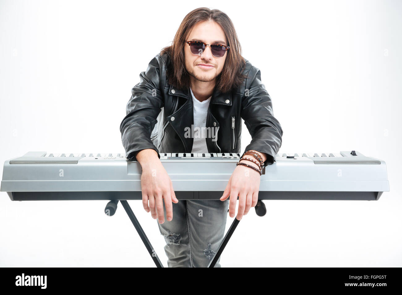 Handsome amusing young man standing and leaning on synthesizer over white background - Stock Image