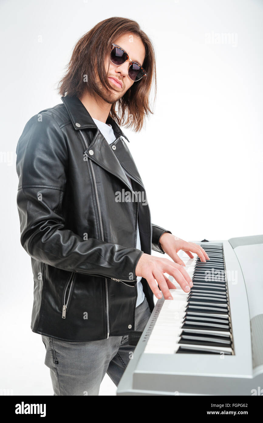 Confident young keyboardist in sunglasses standing and playing on synthesizer over white background - Stock Image