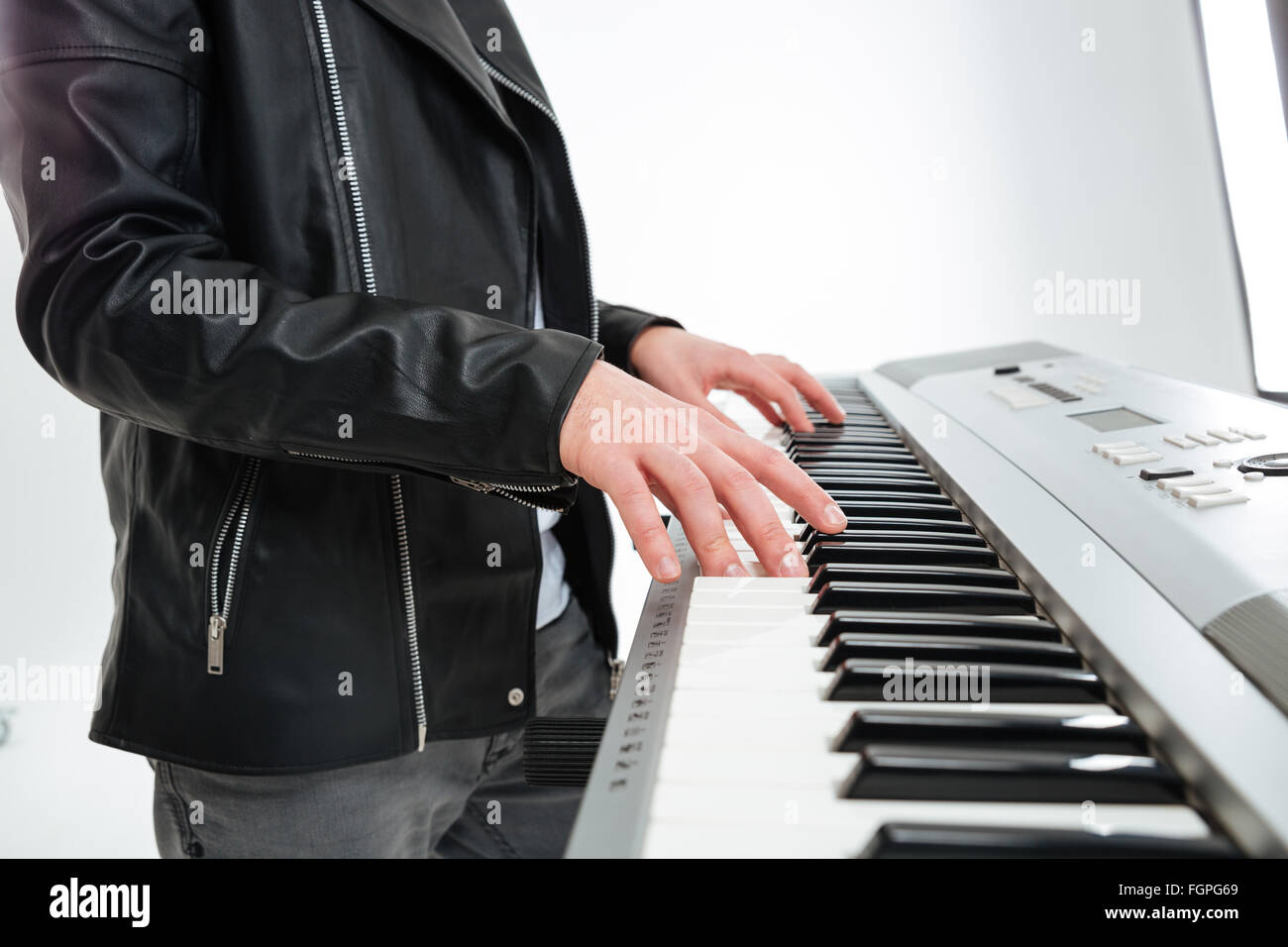 Closeup of hands of young man in black leather jacket standing and playing on synthesizer over white background - Stock Image